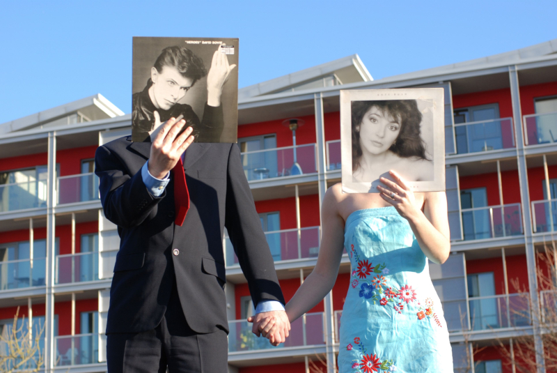 Man and woman holding record album covers up to their faces - Univited Guests Love Letters at Home