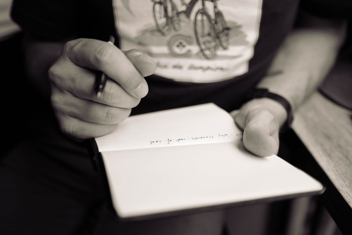 Person writing on notebook by Calum Macauley