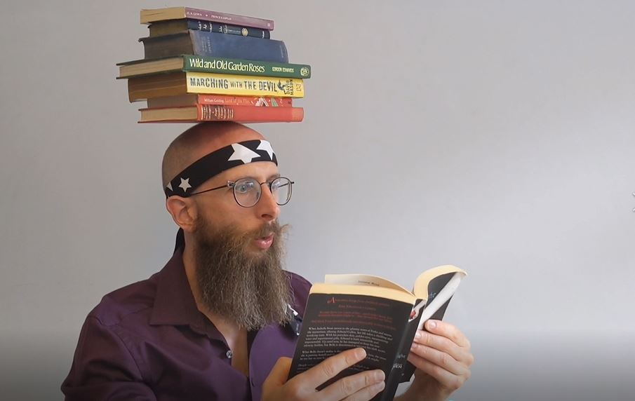 Man with books on head whilst reading from eBooks by TIt for Tat for First Art