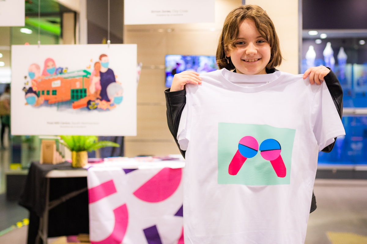 Child holding t-shirt with design created at heat-press workshop